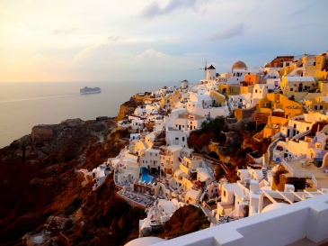 """""""This is a photo of the town of Oia on the island of Santorini in Greece. Oia is the home to most of the white, blue-roofed buildings that Santorini is known for, and is also the most popular spot on the island to watch the sunset. Probably because, as you can see here, the way the light from the sunset hits the town is absolutely stunning."""" -Brynn MacDougall"""